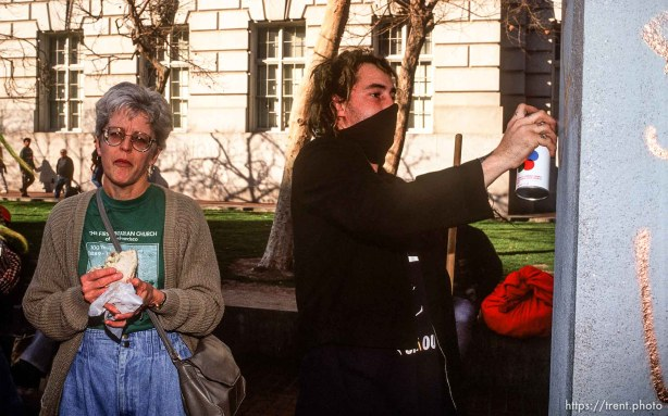 """A member of the self-named """"Punx for Peace"""" spray paints a monument while a woman gives the stink-eye during an Anti-war Gulf War protest."""