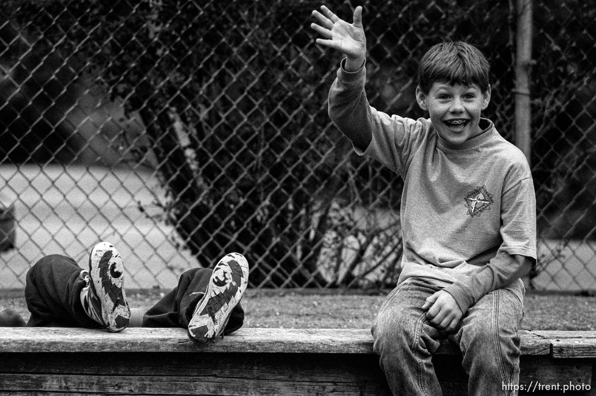 Kids in school P.E. class on bench. one waving, the other has fallen.