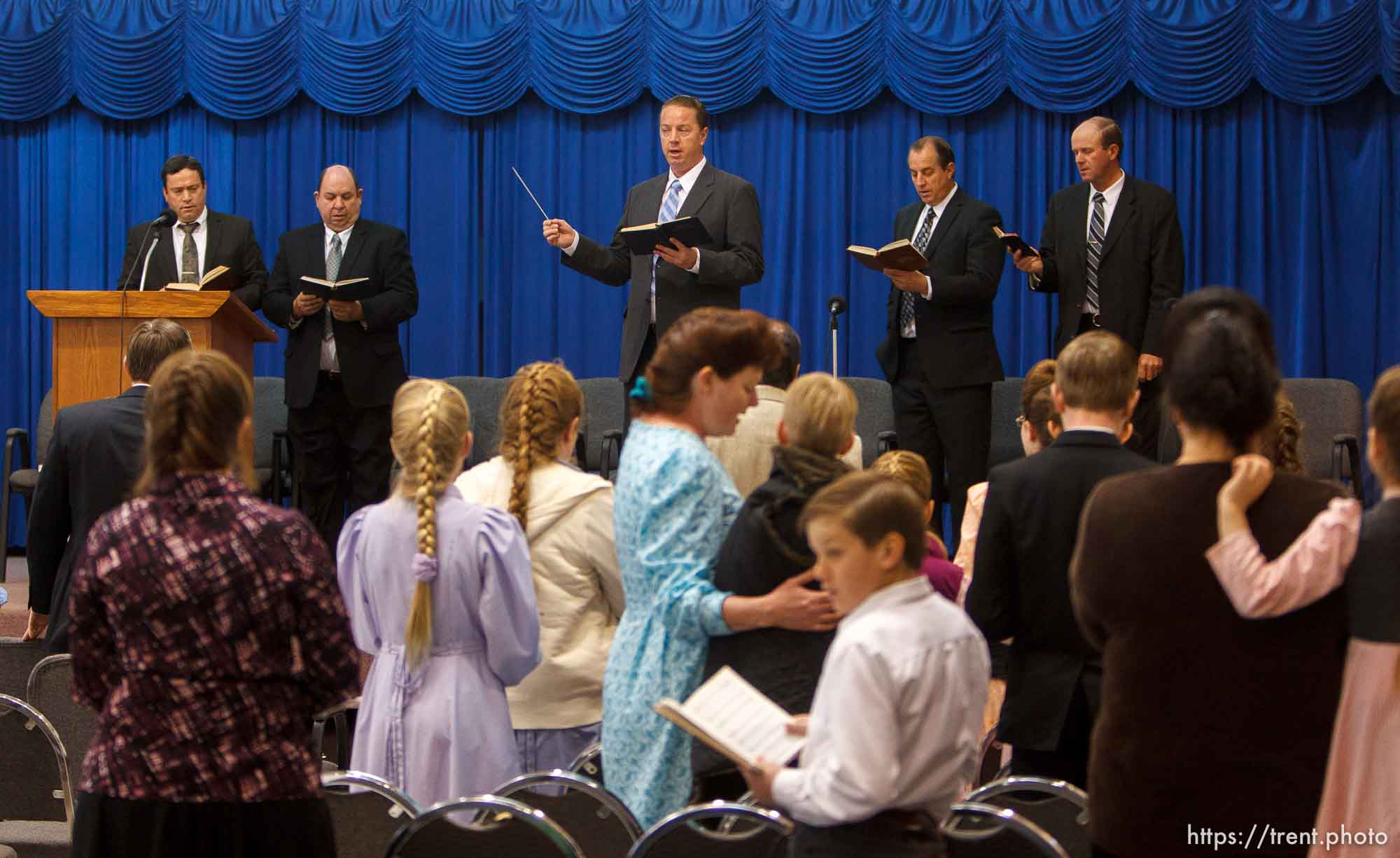 Trent Nelson | The Salt Lake Tribune Sam Allred leads the conjuration in a hymn during a church service of ex-FLDS members Sunday, February 17, 2013 in Hildale. Left to right on stage are William E. Jessop, Garth Warner, Allred, Dan Timpson and Royce Jessop