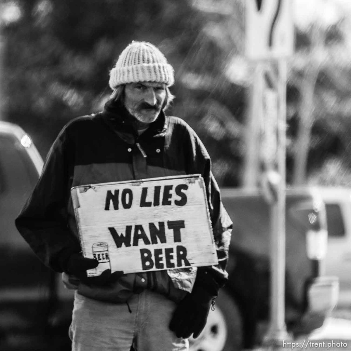 Man holding sign: No Lies, want beer.