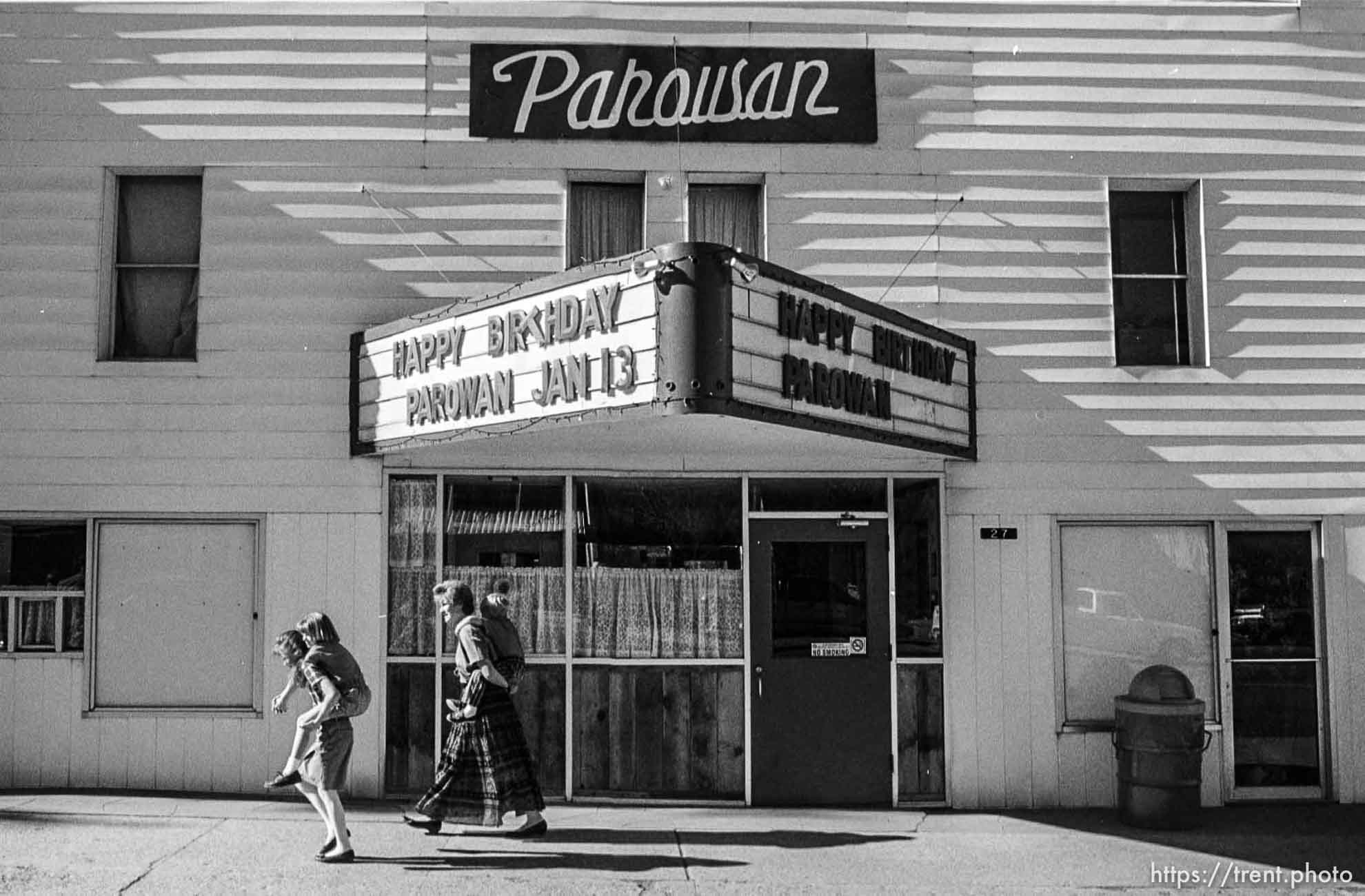 Right to left: Nicole, Ali, Leslie, and Brett Cecil, a Parowan family walk past the Parowan Theater on their way to the dedication ceremony at Heritage Park, Parowan. School busses acting as shuttles from the high school to the park were only half-full as many people opted to walk the five block distance. photo by trent nelson
