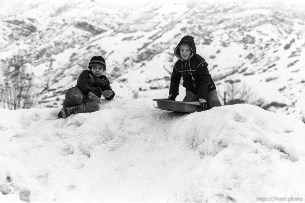 Two boys sledding on snow.