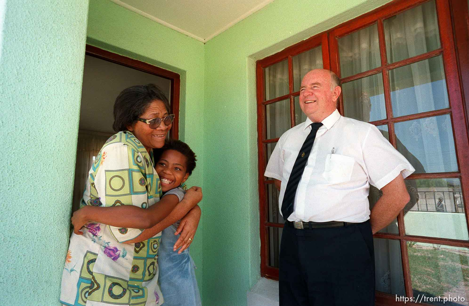 Palesa Smouse hugs her grandmother, Nancy, while Clive Nicholls stands near.