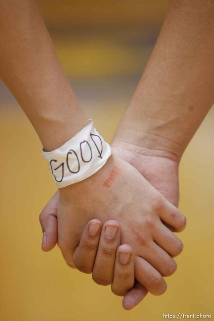 """Bingham players holding hands with """"good"""" wristbands. Taylorsville - Bingham wins the state championship. Bingham vs. Skyline High School, 5A Girls State Basketball Championship game at Salt Lake Community College."""
