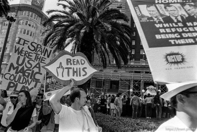 Protest signs including middle finger at Act-Up protest during visit of President Bush