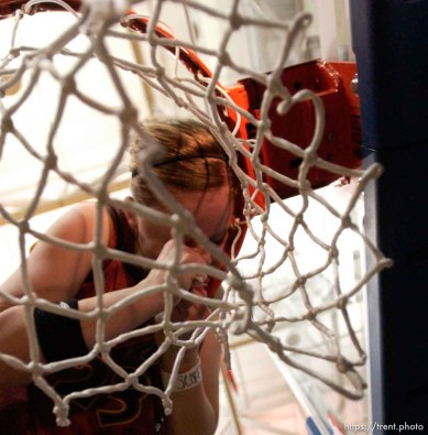 Taylorsville - Mountain View's Lindsay Moore bites tape to loosen the net, celebrating as Mountain View defeats Timpview girls high school basketball, 4A state championship game, Saturday afternoon at Salt Lake Community College. Photo by Trent Nelson/The Salt Lake Tribune; 02.28.2004