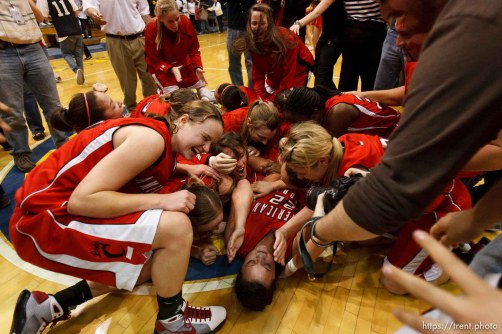 Taylorsville - American Fork players collapse in a dog pile at center court, celebrating their championship win over Riverton. Riverton vs. American Fork High School girls basketball, 5A State Championship game Saturday February 28, 2009 at Salt Lake Community College.