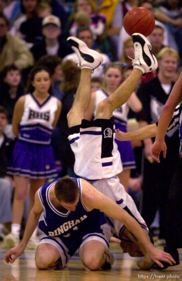 Riverton's Andrew Nuttall is upended going after the ball and over Bingham's Mike Higgins during Friday night's matchup. Bingham defeats Riverton, basketball.