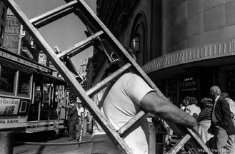 Man carrying ladder. Leica hip shots on the street.