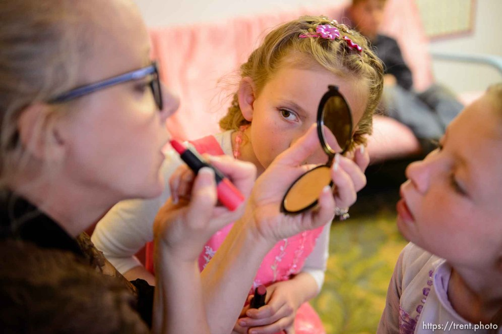 (Trent Nelson | The Salt Lake Tribune) A princess party was thrown for several young FLDS girls in Colorado City, Ariz., Friday March 16, 2018, as a reward for reading books. Before the party, Christine Marie Katas, left, of Voices for Dignity, emphasized the importance of education to Kathy, center, and Lolly Bistline while giving them their first experience with makeup.