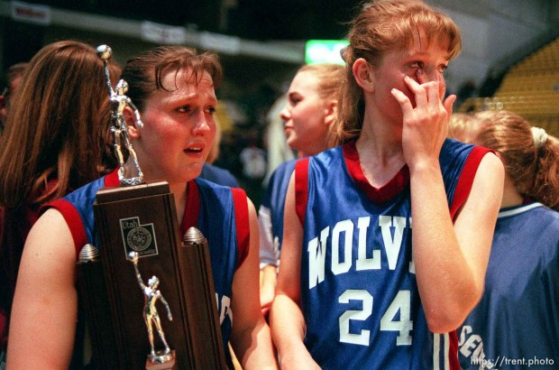 North Sevier basketball players Ann Braithwaite and Shadoe Shaheen (left) hold the second place trophy and grieve while the state champion Beaver Beavers celebrate their victory.