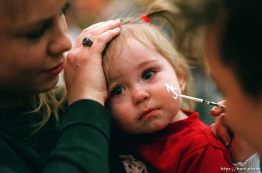 """17-month-old Katie Childs has """"NS"""" (for North Sevier) painted on her face by cheerleader Jennifer Brown (right). She is held by Marcee Hampton (left). This is prior to the girls game for the state championship."""