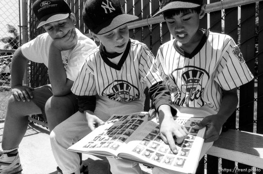 Kids reading yearbook in dugout at Yankees baseball game.