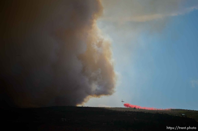 (Trent Nelson | The Salt Lake Tribune) A plane dropping retardant on the Dollar Ridge Fire is dwarfed by smoke, in Duchesne County, Tuesday July 3, 2018.