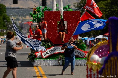 (Trent Nelson | The Salt Lake Tribune) The Days of '47 Parade in Salt Lake City, Tuesday July 24, 2018. Two BYU fans rush out to wave their flags in front of the University of Utah's float.