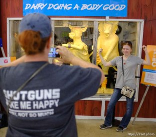 i(Trent Nelson | The Salt Lake Tribune) Lauren Pearce poses for her mother Katrina in front of the Utah Butter Cow Sculpture at the Utah State Fair, Sunday Sept. 9, 2018.