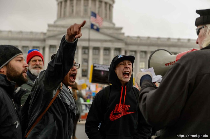 (Trent Nelson | The Salt Lake Tribune) Protesters try to drown out a man trolling them with a megaphone at a rally against a visit by President Donald Trump, Monday December 4, 2017.