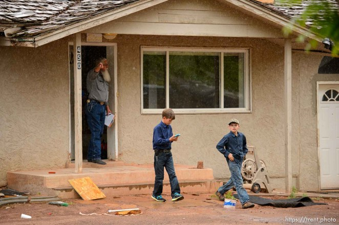 Trent Nelson | The Salt Lake Tribune The locks are changed on an empty home in Colorado City, AZ, Tuesday May 9, 2017, as part of the UEP Trust evictions. FLDS children take videos of the work of locksmith Kelvin Holdaway, and are then ordered off the property by Mohave County Constable Mike Hoggard.