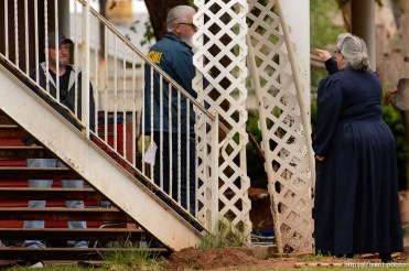 Trent Nelson | The Salt Lake Tribune FLDS member Shannon Darger confronts UEP Trust agent Ted Barlow and Mohave County Constable Mike Hoggard as they change the locks on her Colorado City, AZ, home, Wednesday May 10, 2017. Like other FLDS members, Darger considers working with the UEP Trust to be against her religious beliefs and has chosen to move her family out of state rather than sign an occupancy agreement with the trust. At right, one of Darger's children takes video of the confrontation.