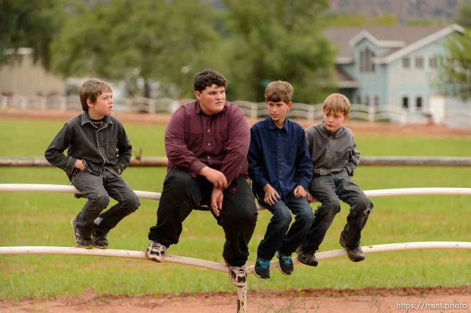Trent Nelson | The Salt Lake Tribune Four FLDS boys sit on a fence watching as the UEP Trust takes control of a Colorado City, AZ, home, Wednesday May 10, 2017. Second from left, Marvin Darger, had been living in the home and is now moving out of state with his family.