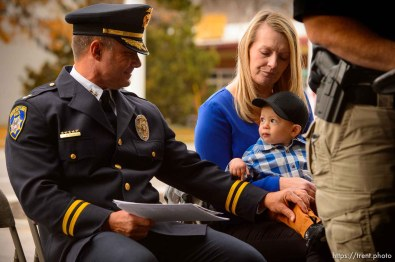 (Trent Nelson | The Salt Lake Tribune) South Salt Lake Police Deputy Chief Dwayne Ruth reaches out to Jackson Romrell at the dedication ceremony of the David P. Romrell Public Safety Building on Sunday Nov. 24, 2019. The building is named after Officer Romrell (Jackson's father), who was killed in the line of duty on Nov. 24, 2018 - one year ago. Holding Jackson is Jennifer Romrell Legerski, Officer Romrell's sister.
