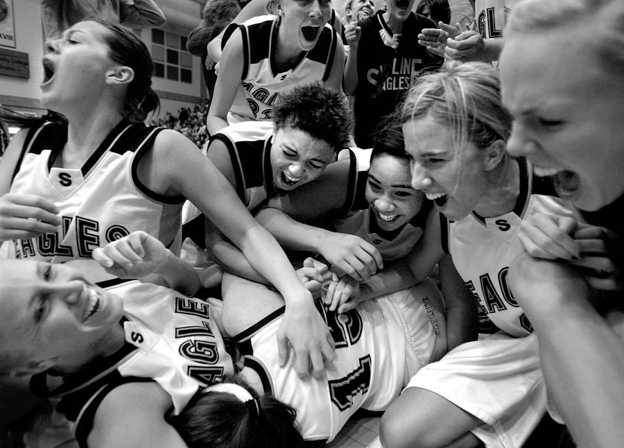 Skyline High School's basketball team dogpiles on Liz Johnson (15, bottom) after Johnson hit a last second shot to beat Davis and send Skyline to Saturday's State Championship game.
