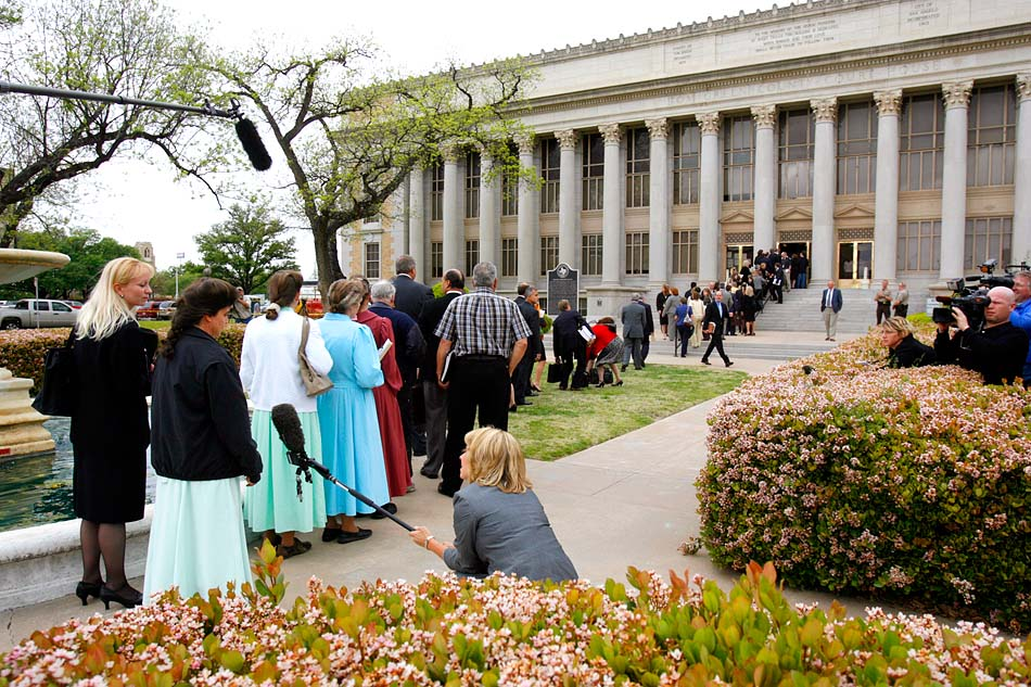 San Angelo, Texas - Hundred of attorneys, officials, and FLDS members lined up to get through security and into the Tom Green County Courthouse for the initial 14-day hearing to decide the fate of the 416 children removed in the raid on the FLDS Church's YFZ Ranch. As each child and parent were entitled to a state-appointed attorney, the hearing was quickly bogged down with objections from dozens of attorneys. After two long days of hearings, including twenty-one hours of testimony, Judge Barbara Walther ruled that CPS could keep the FLDS children in foster care until at least the next hearing, scheduled for two months after the raid began.