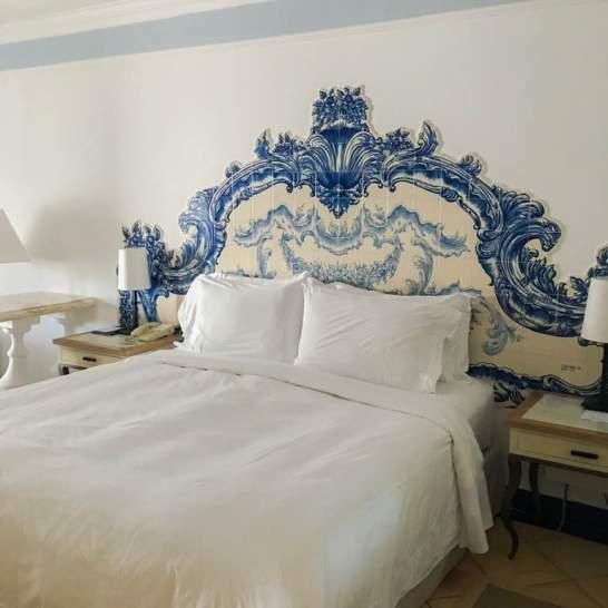 Il letto è sormontato da una preziosa spalliera dipinta a mano, nella tonalità tipica dell'Algarve che richiama i colori del mare.
