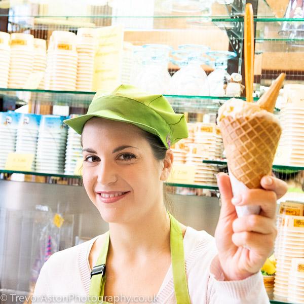 Woman in ice cream parlour serving an ice cream cone Trevor Aston Photography