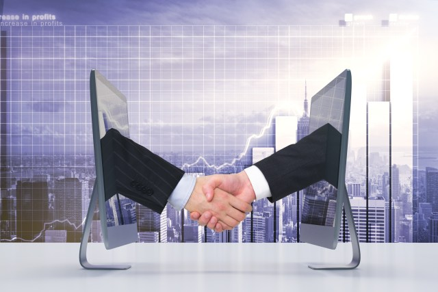 Handshake of two monitors via the Internet, business concept