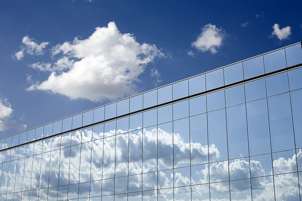 Clouds reflected in the glass windows panels of an office building.