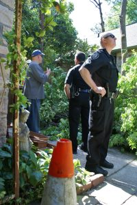 Two Greensboro police officers listened and surveyed the damage.