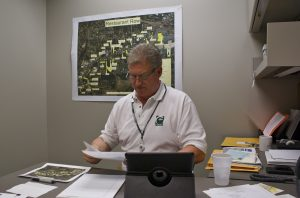 Wilkins sits at his desk in front of the large map of the restaurant row area.