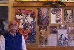 """CW """"Chuck"""" Eldridge poses in front of Tattoo Archive's newest exhibit on Japanese tattooing."""