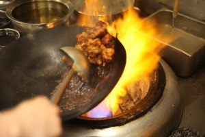 A searing-hot wok crisps the chicken used for America's favorite Chinese takeout menu item.