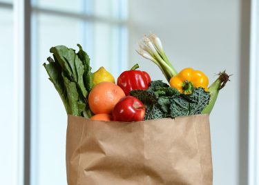 Fruits and vegetables in grocery bag and on wooden table