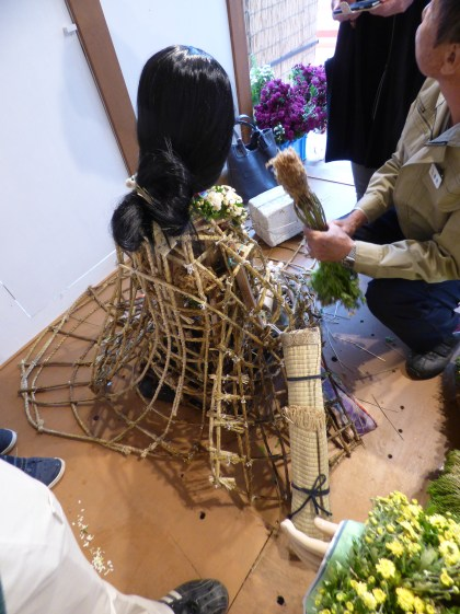 The process of making a mum doll involves placing a moss-wrapped mum plant into a woven framework