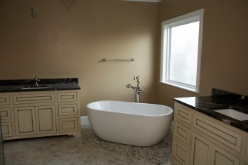 Large soaking tub, with his and hers matching vanities on either side.