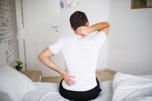 Man suffering from back pain at home in the bedroom