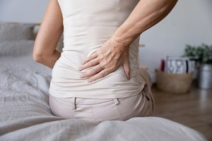woman sitting on bed experiencing lower back pain due to degeneration
