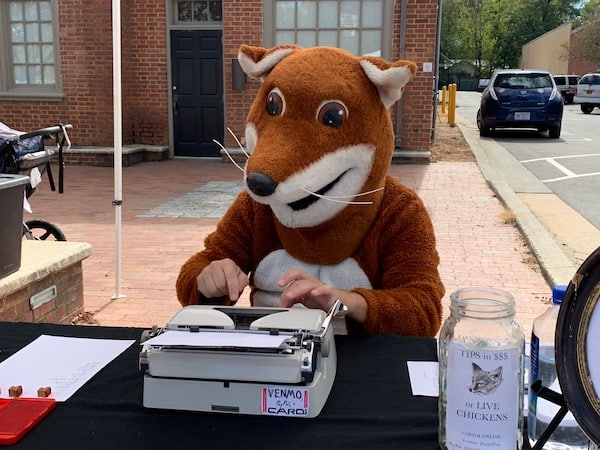 poet dressed as a fox typing a poem on a vintage typewriter