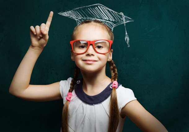 small girl in red glasses and graduation cap