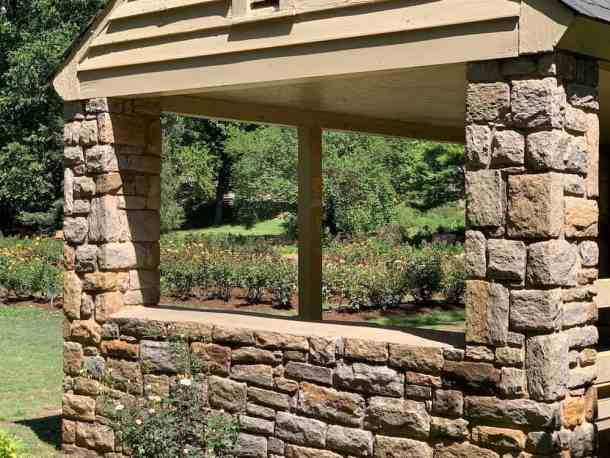 view of roses through windows of stone shelter at Raleigh Rose Garden