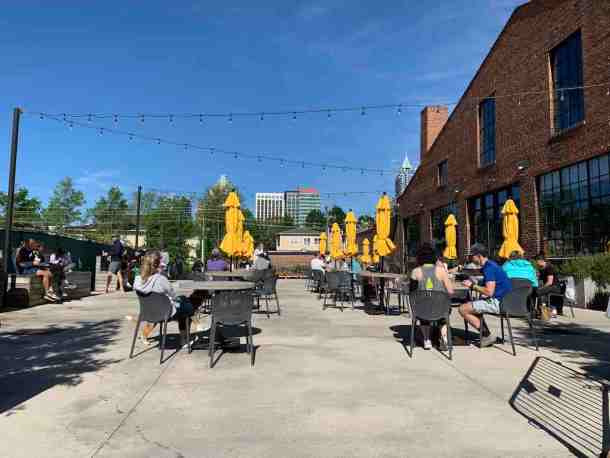 patios with table with yellow umbrellas at transfer co food hall in raleigh