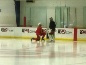 Kevin Westgarth stretches while talking with Cam Ward - Peter Koutroumpis, Triangle Sports Network