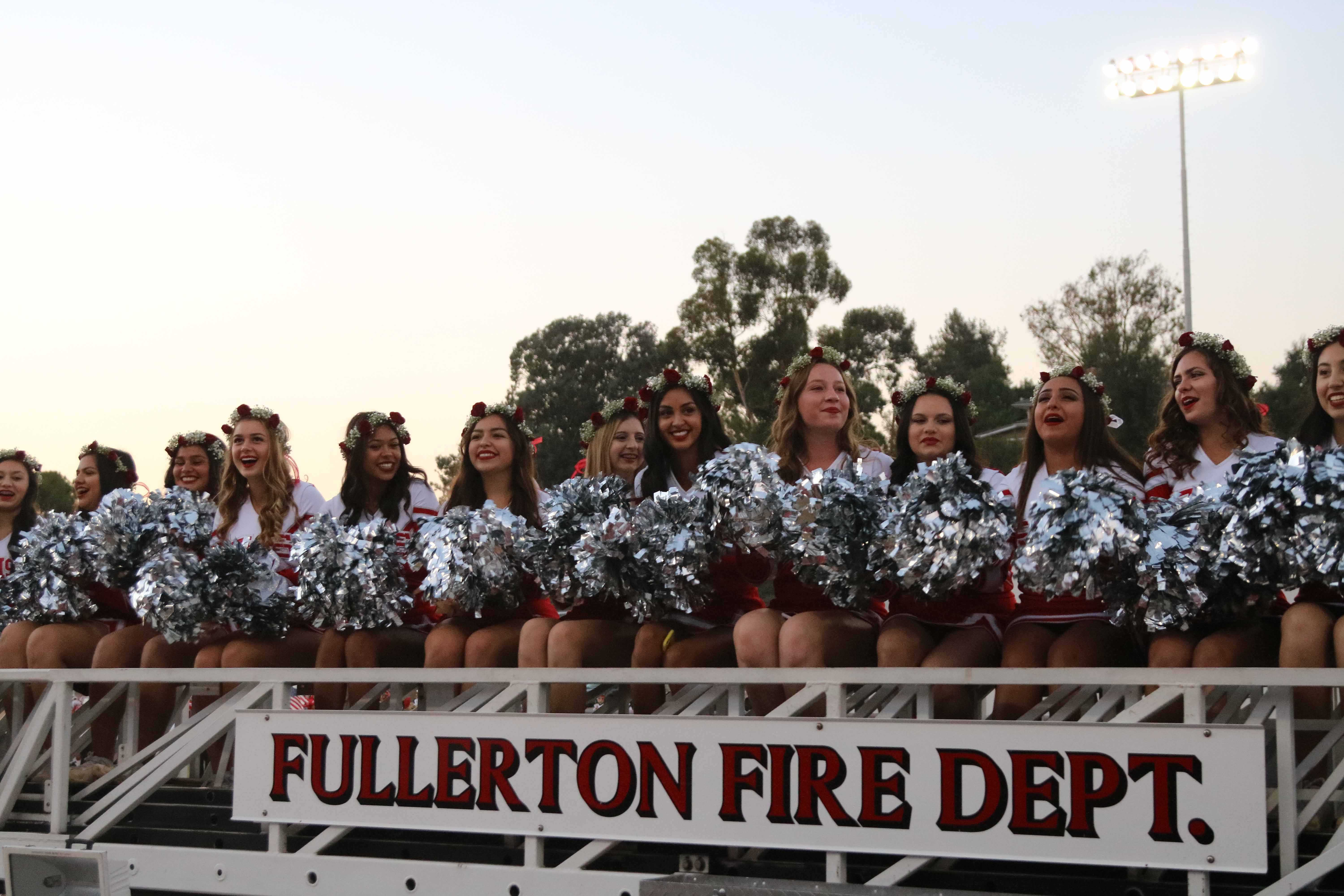 FUHS+Varsity+Cheer+rides+past+the+crowd+on+a+firetruck+at+the+Homecoming+game+on+Sept.+16.++Photo+by+Emily+Caluya.+