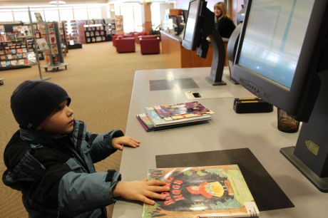 A young patron checks his book out at the self checkout station in a Lake County library. Sheryl DeVore/Tribune