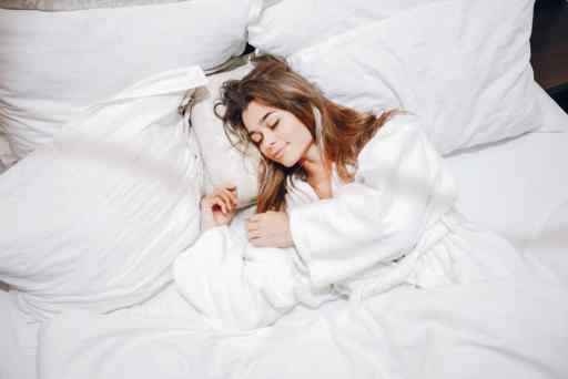 Beautiful girl in a white bathrobe. Lady lying in a bed