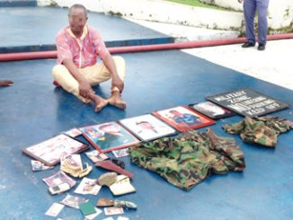 """A fake officer of the Nigerian Navy was, on Thursday, in Warri, Delta State, paraded before journalists for impersonation. The impersonator, Mr Ushi Prince Moses Okeimutie, was caught with 10 identity cards, a camouflage uniform, a pistol, a horsewhip, seven photographs and five portraits where he adorned himself in naval uniforms and paraphernalia. Other items included a mobile phone and a signboard with the inscription: """"Military Zone, No loitering, No parking, keep off!"""" with which he was deceiving the people. Commander, Nigerian Navy Ship (NNS DELTA), Warri Naval Base, Commodore Joseph Dzunwe, who assumed office a few weeks ago, said the impersonator had defrauded several unsuspecting Nigerians before his arrest recently. The naval boss said at times, the suspect would appear as an officer of the navy and at other times, as a naval rating, depending on who he wanted to defraud. The suspect, who is in his 50s, did not argue when he was asked to narrate his side of the story. He simply said he was arrested in his home for parading himself as a naval personnel and that he started the fraudulent practice about seven months ago. """"Truly, impersonating is embarrassing. It has not been long that I started the business. Actually, I was ignorant of the fact that my action was criminal. I have been in the business for about seven months,"""" he disclosed. Ushi added that he was not really pushed into the crime by joblessness or any other societal factor. Speaking further on the suspect, Commodore Dzunwe said: """"He is an impersonator. He has been impersonating the navy and we recovered items from his house. """"He has taken pictures in various military uniforms and there was a report that he used them to intimidate and extort from members of the public. """"In one of the pictures, he is a lieutenant in the navy; in another one, he's a sub-lieutenant, and yet in another, he is a rating."""" The naval boss promised to hand over the suspect to the Nigeria Police for further investigations """