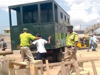 KAI Official forcing a man inside a Black Maria, for crossing the Ketu Expressway. Photo: Sylvester Okoruwa